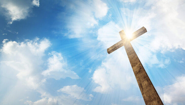 A wooden Christian cross with bright sun and clouds. - You Are Not A Nobody, You Are Chosen