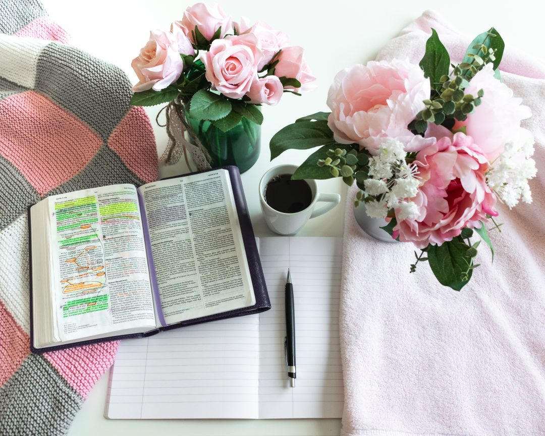 Pink Bible flat lay: Bouquet of pink roses, open Bible, black tea, coffee, journal, notebook, pen and pink blankets. Morning devotional. Rose, white, grey tones.