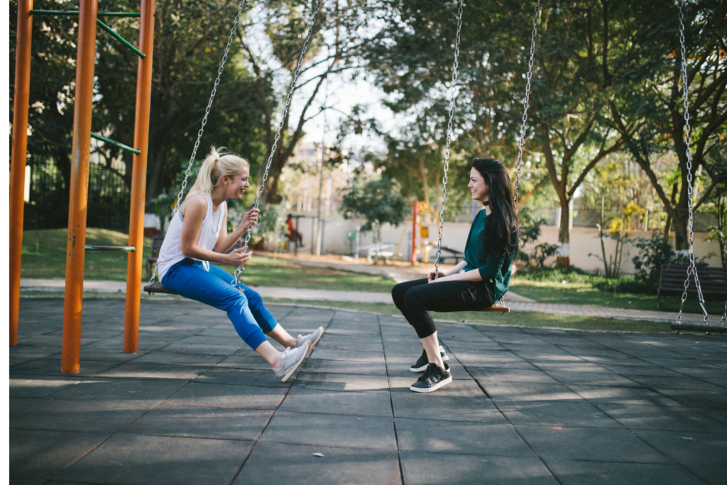 Women laughing and talking together on swings
